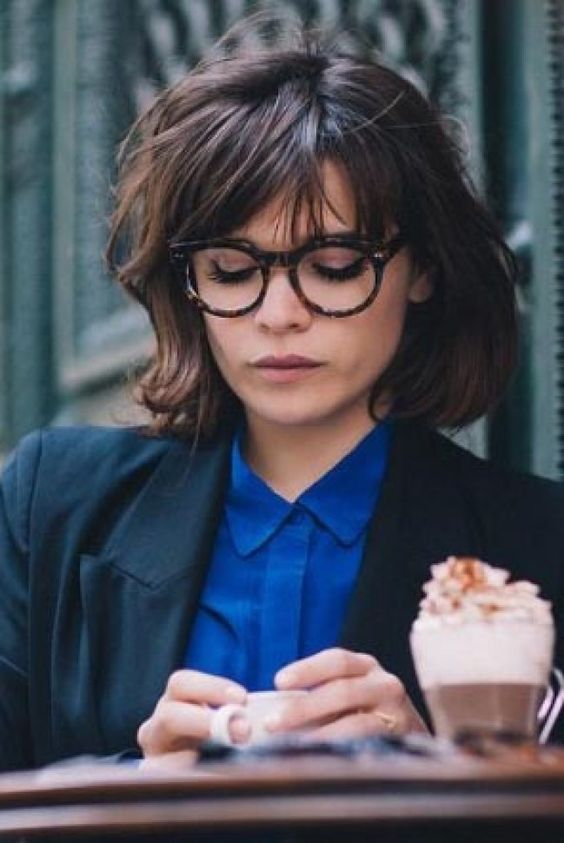 a short messy bob worn with a long French fringe and trendy glasses