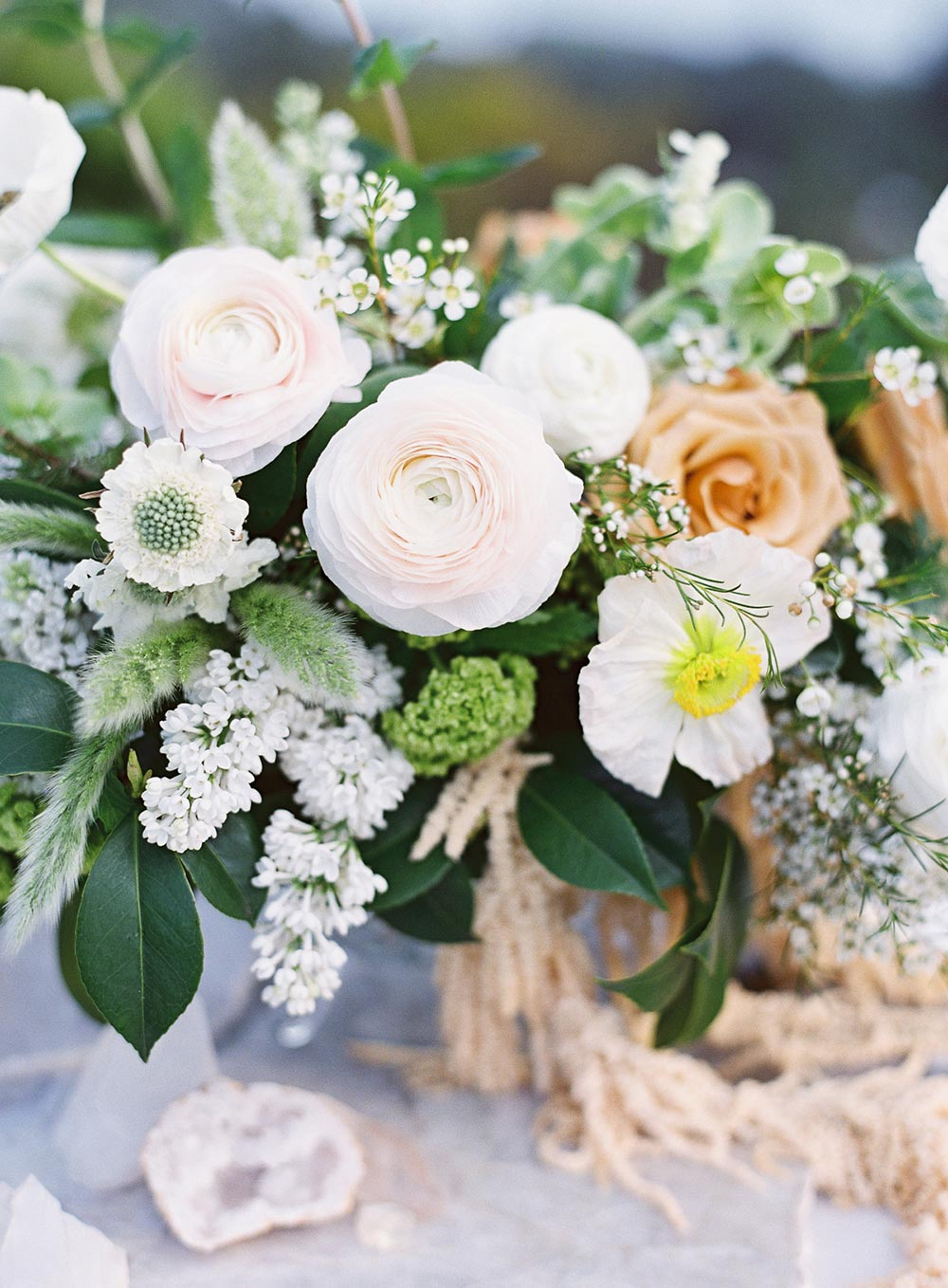 cream ranunculi and peach rose wedding centerpiece