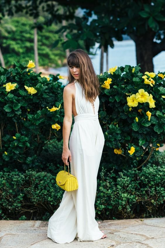 a white fitting plunging neckline jumpsuit with culottes and a neone yellow little bag for a wow effect