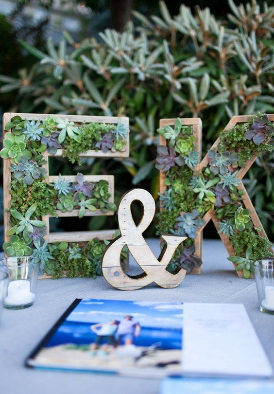wooden monograms with succulents planted inside are a creative and modern wedding decor idea