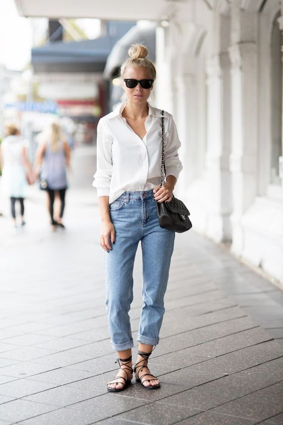 a white button down blue cuffed jeans, black lace up sandals and a black bag