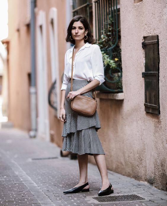 a white button down, a ginghm ruffle skirt, black flat shoes and a brown bag