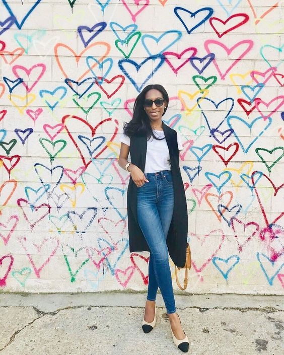 blue high waisted skinnies, a white tee, a black long vest and creamy and black flats