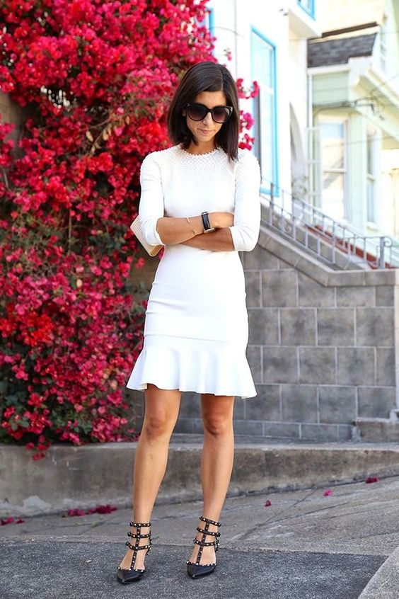 a white long sleeve dress with a high neckline and a texture, a pleated skirt, black sutdded shoes for a modern bride