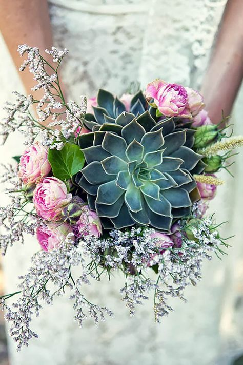 a gorgeous wedding bouquet with a large succulent, some lilac and pink blooms around