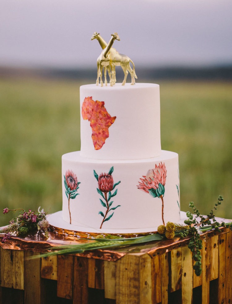 The wedding cake was with handpainted king proteas, African continent and gold giraffe cake toppers