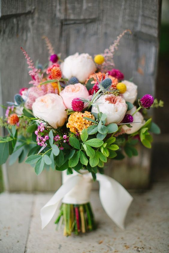 a gorgeous colorful bouquet with blush peonies, greenery, blue thistles and bold orange, yellow and pink clover