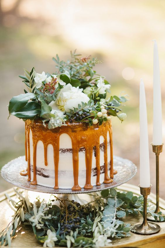 a caramel drizzle wedding cake with lush greenery and white blooms on top for a garden or woodland wedding