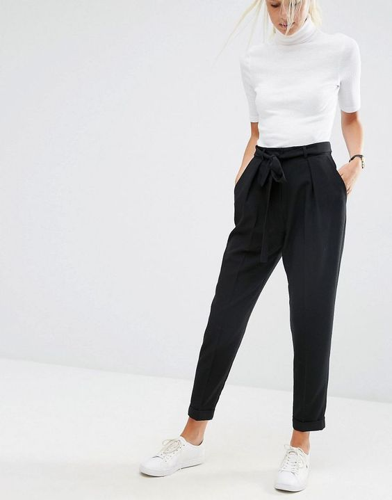 black pants with pockets and a draped top, a white top and sneakers for a business casual look