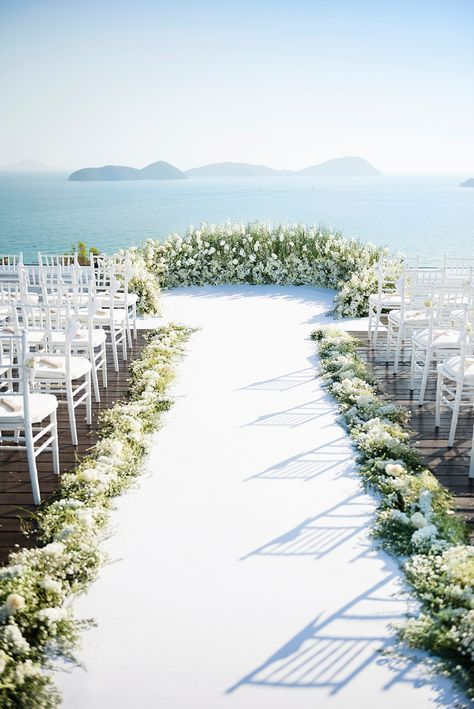 a luxurious white bloom and greenery semi circle wedding altar, the same lining for the aisle and a gorgeous seascape
