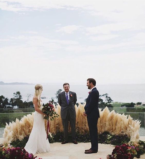 a gorgeous greenery, pampas grass and plum-colored bloom wedding altar for a boho feel