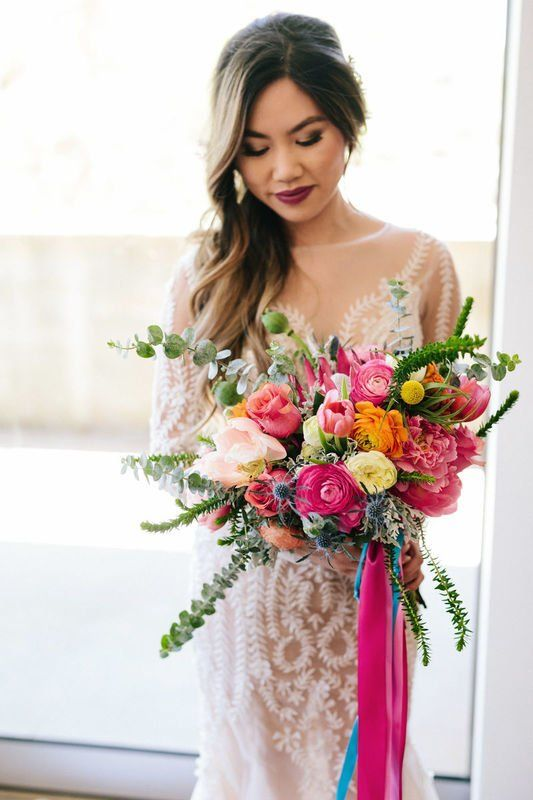 a summer wedding bouquet with pink, orange and blush flowers, greenery and colorful hanging ribbons