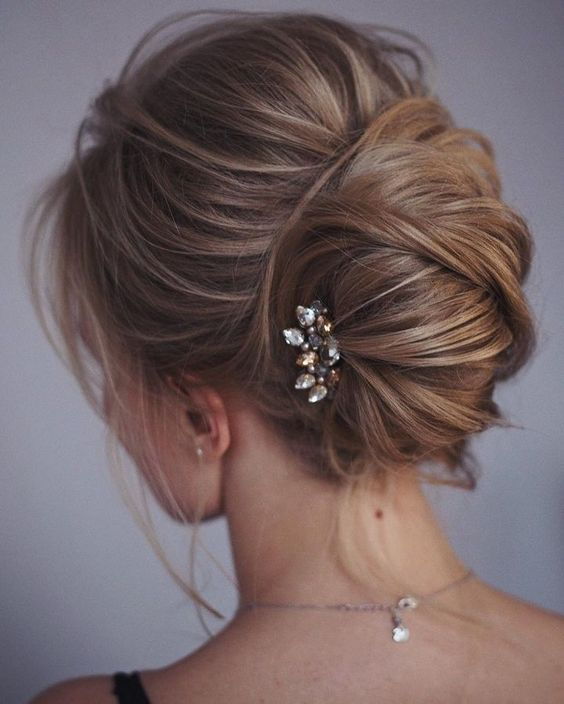 one more catchy idea of a messy chignon and twists and locks down and a small rhinestone hairpiece
