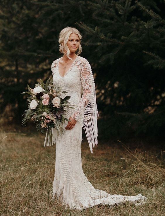 a sheath boho lace wedding dress with a train and a fringed cape on the shoulders