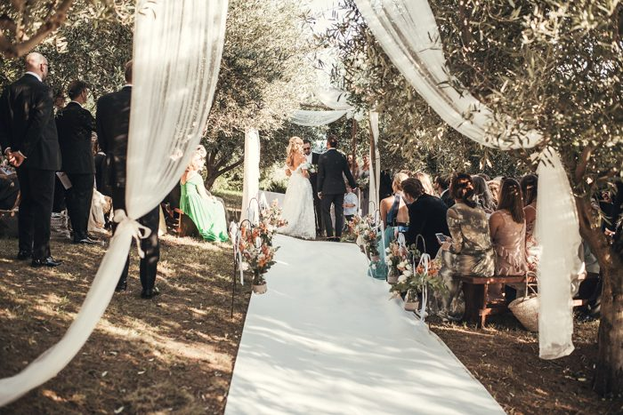 The wedding ceremony space was placed in an olive grove and with airy fabric