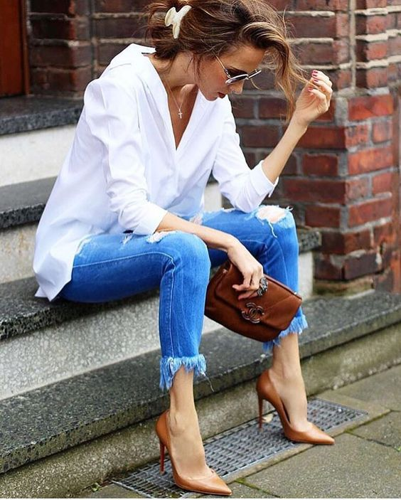 a white shirt, blue ripped and fringe skinnies, brown heels and a clutch for a casual look