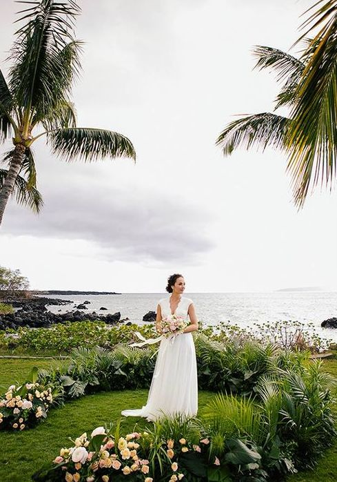 a lush tropical wedding arch of palm leaves and blush blooms lets enjoy a seascape