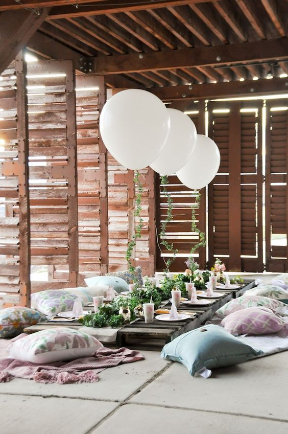 a garden bridal shower picnic inside a sunroom, greenery, white balloons and pillows right on the floor