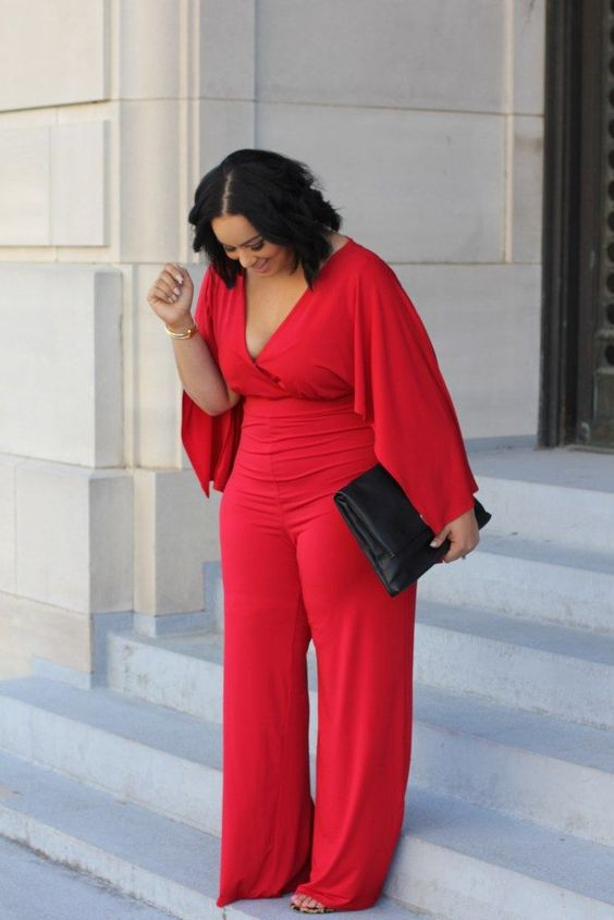 a gorgeous red jumpsuit with wide sleeves, a deep V-neckline and wide pants to show off all the curves