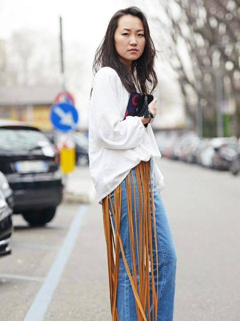 With white loose shirt, jeans and printed clutch