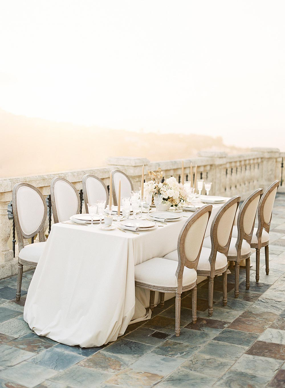balcony wedding tablescape with cushioned dior chairs and cream table linens
