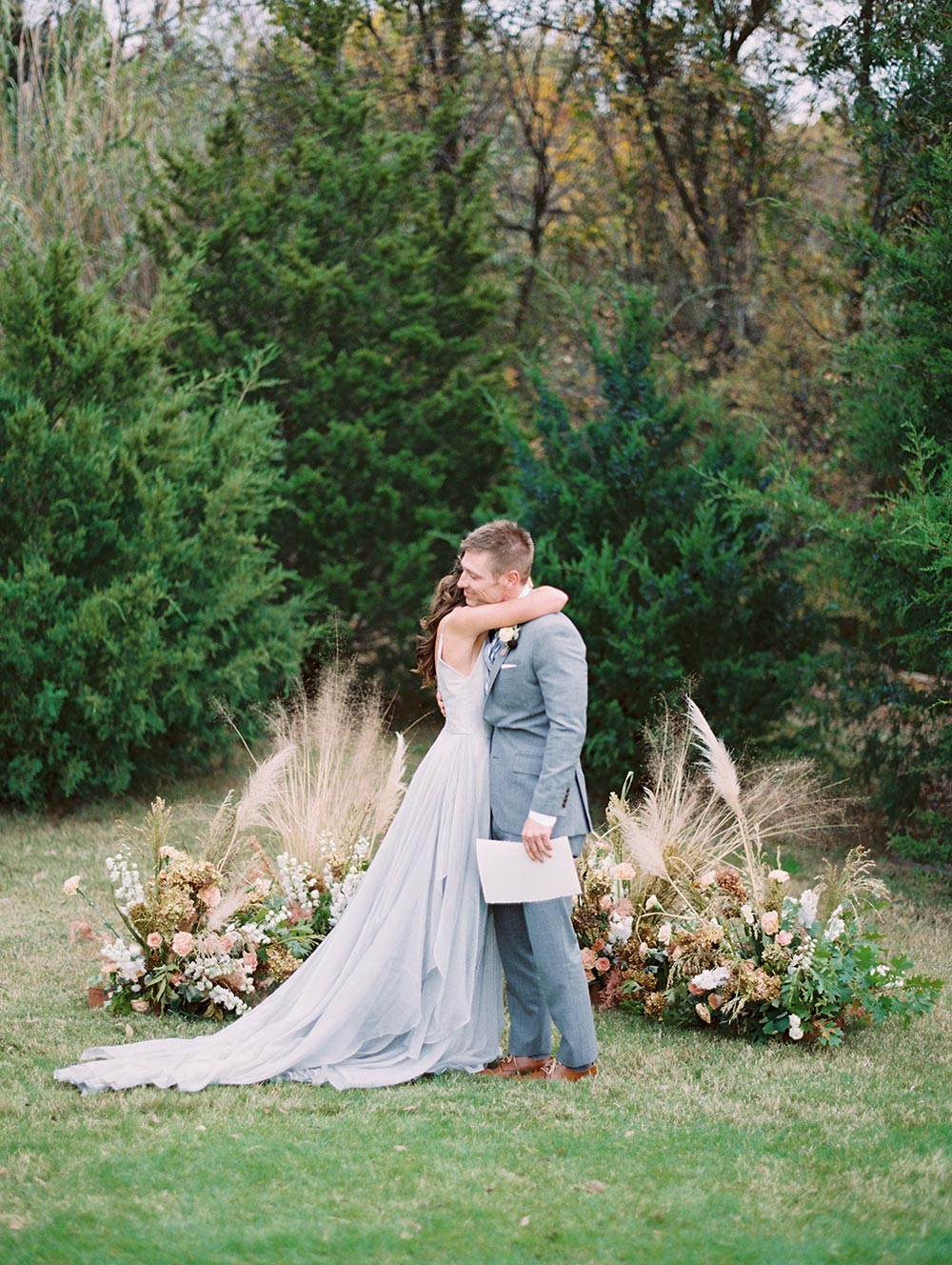 pampas grass wedding ceremony backdrop and dusty blue layered organza wedding dress