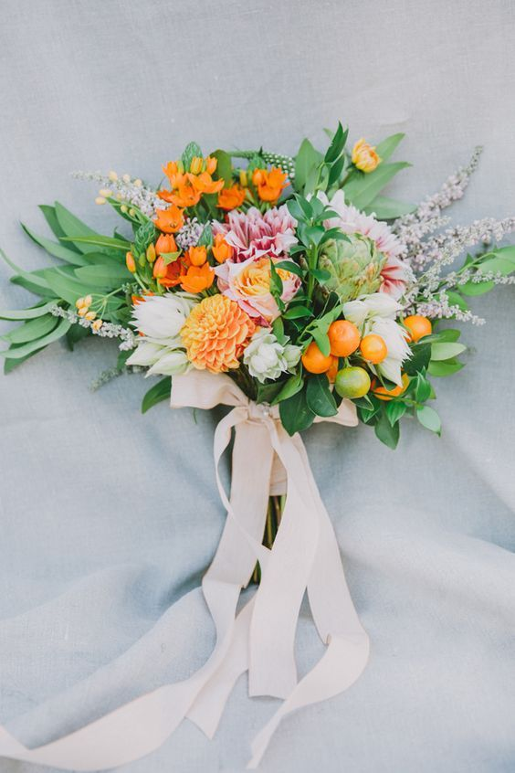 a wedding bouquet in the shades of orange, cream and pink, with greenery and litle kumquats plus blush ribbons