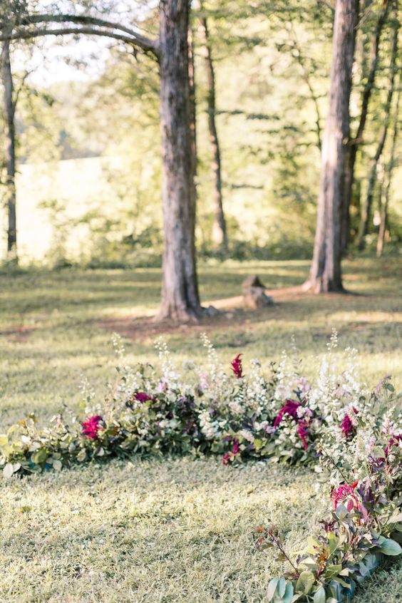 a greenery, herbs and plum-colored blooms woodland wedding arch looks very natural as if plants are growing here