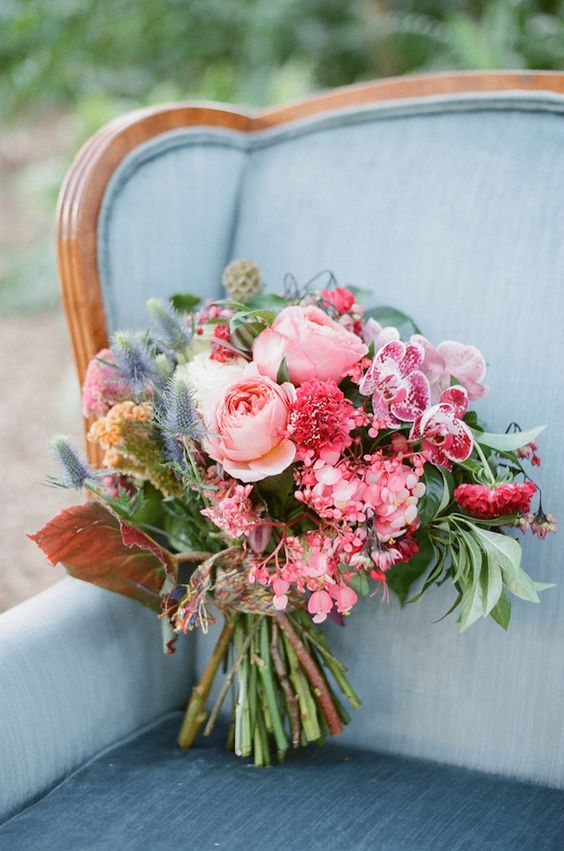 a super colorful wedding bouquet in the shades of pink and blue with various leaves