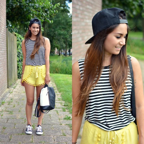 With striped top, black cap, sneakers and black and white backpack