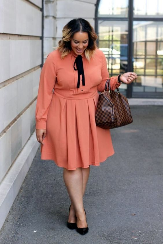 a bright orange knee dress with a pleated skirt and a black ribbon bow, a checked bag and black heels for a bold work look