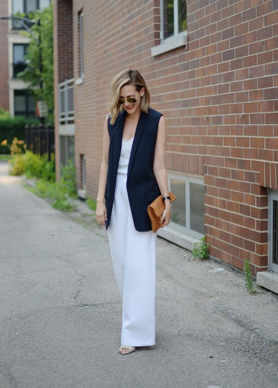 white wide pants, a white sleeveless top, a navy long vest, heeled sandals with a brown clutch