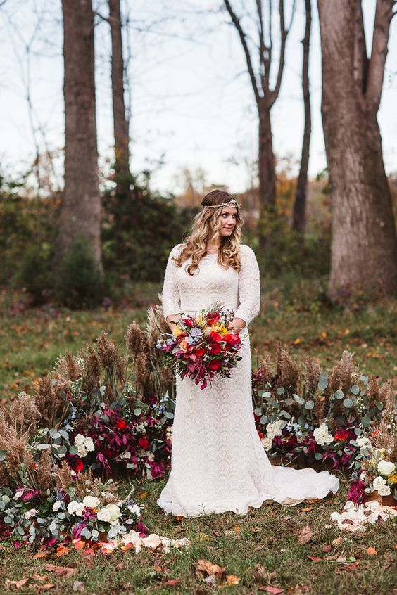 a gorgeous boho fall wedding altar with dried grasses and leaves, greenery and plum-colored blooms