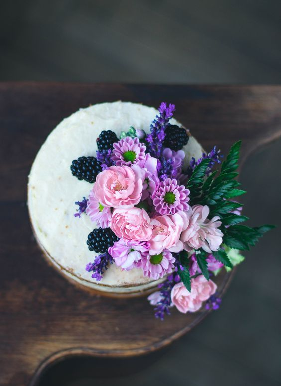 a vanilla lavender naked cake with pink and purple blooms and blackberries