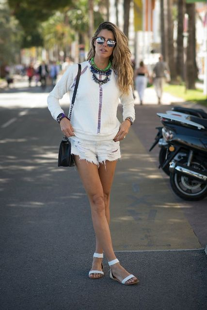 With white shirt, white distressed shorts, black bag and necklace