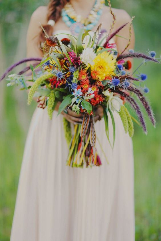 a colorful boho ethnic wedidng bouquet with orange, yellow blooms, blue thistles, lisianthus and woven ribbons