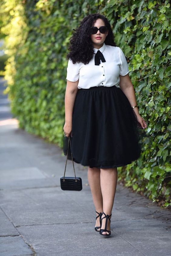a black full skirt, a white blouse with black buttons and a bow and black shoes
