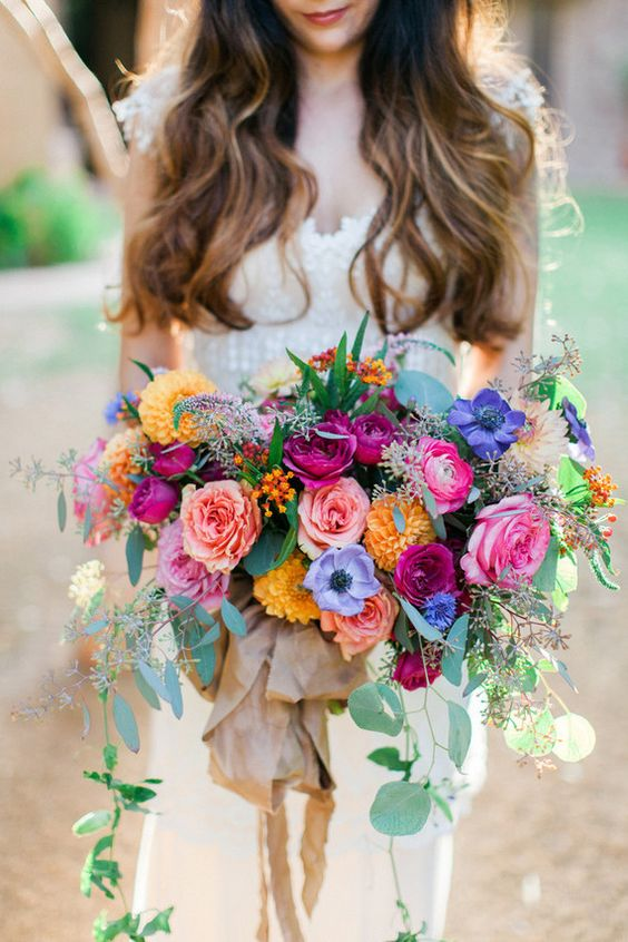a lush colorful bouquet in pink, yellow, purple and fuchsia plus eucalyptus
