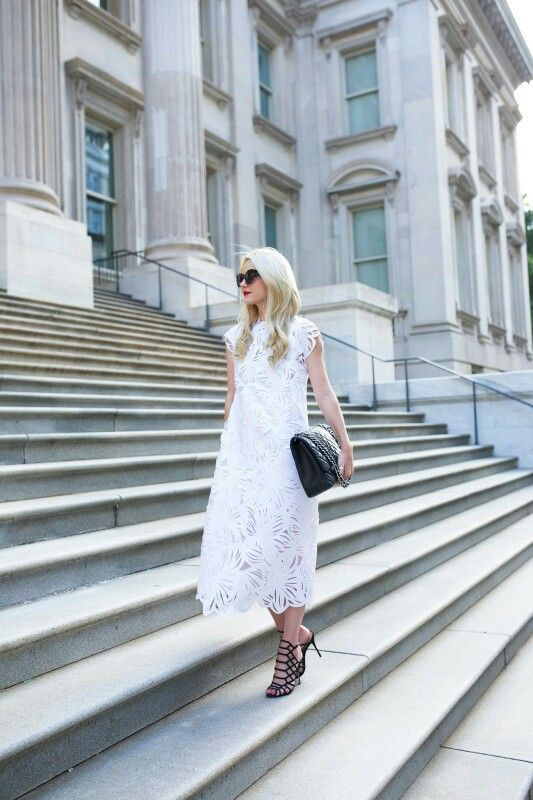 a loose white lace midi dress with cap sleeves and a high neckline, black laser cut shoes and a large black clutch