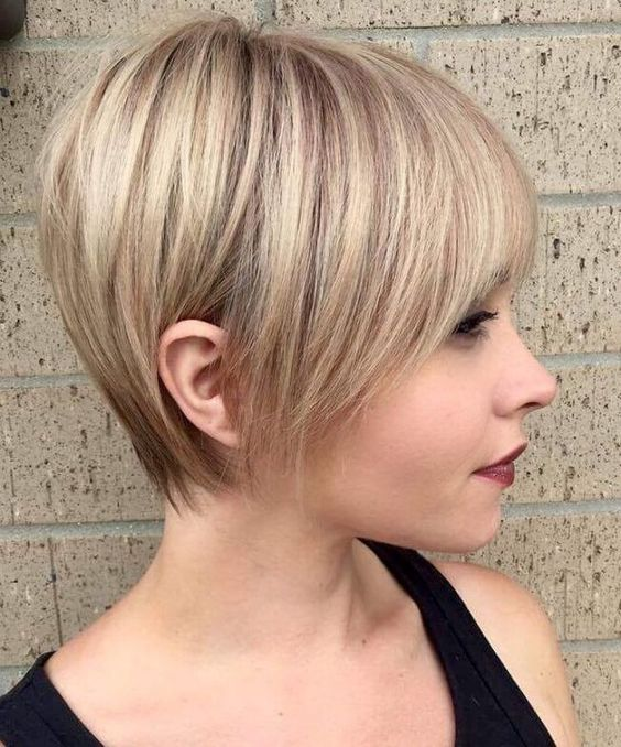 a longer pixie haircut with sleek styling and a light blondie balayage