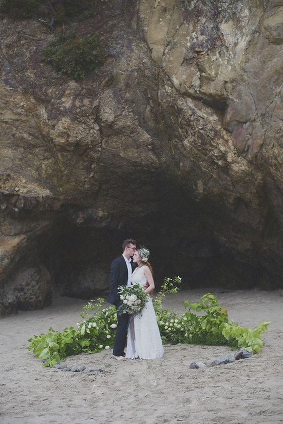 a lush greenery wedding arch with some white blooms and pebbles right on the beach