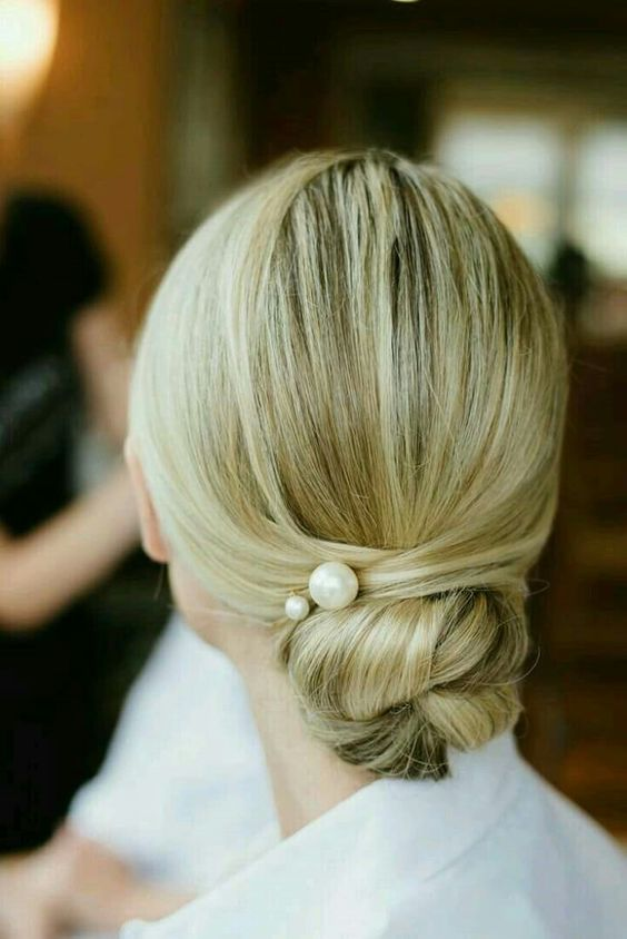 a twisted low bun with pearl pins and a sleek top for a modern take on a traditional look