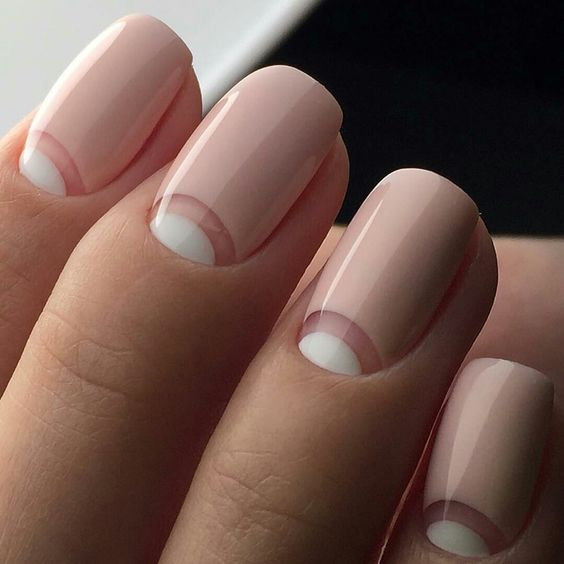 a fresh take on French manicure with half moon whites and light pink base is an edgy idea