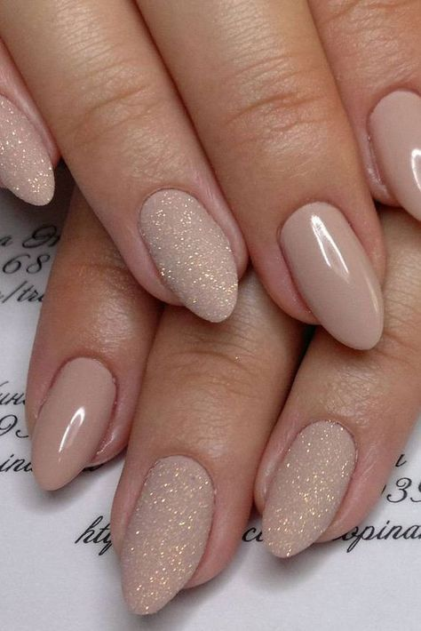 nude manicure with touches of glitter on some nails will add a glam feel to your look