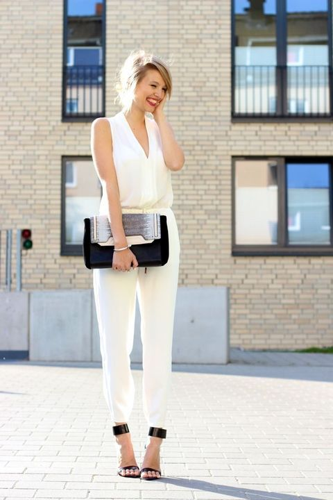 a white sleeveless fitting jumpsuit with a V-neckline, black ankle strap shoes and a matching clutch for a modern bride