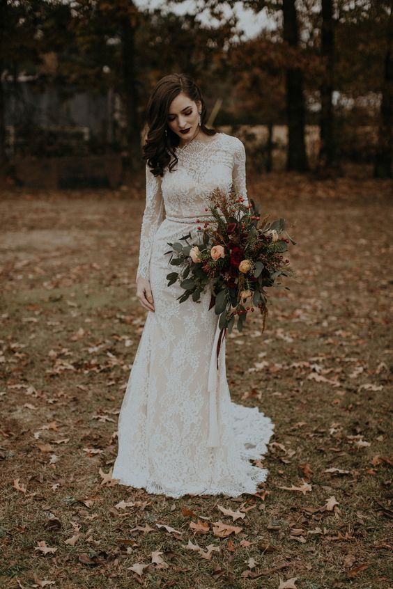 a lace sheath wedding dress with long sleeves, a high neckline and a sash plus statement earrings