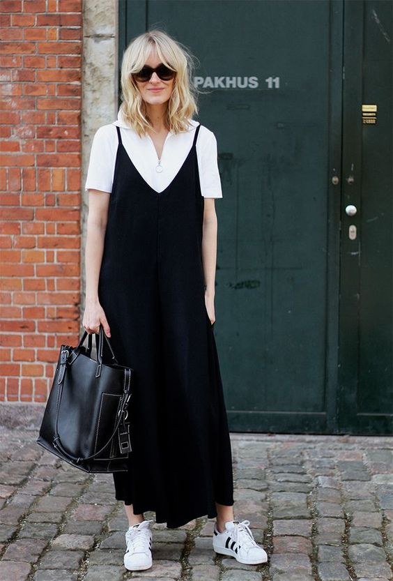 a white polo shirt, a black slip dress over it, white sneakers and a comfy bag