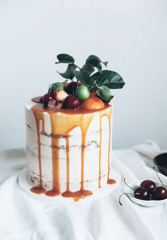 caramel drizzle semi naked wedding cake topped with citrus, cherries and fresh leaves for a summer wedding