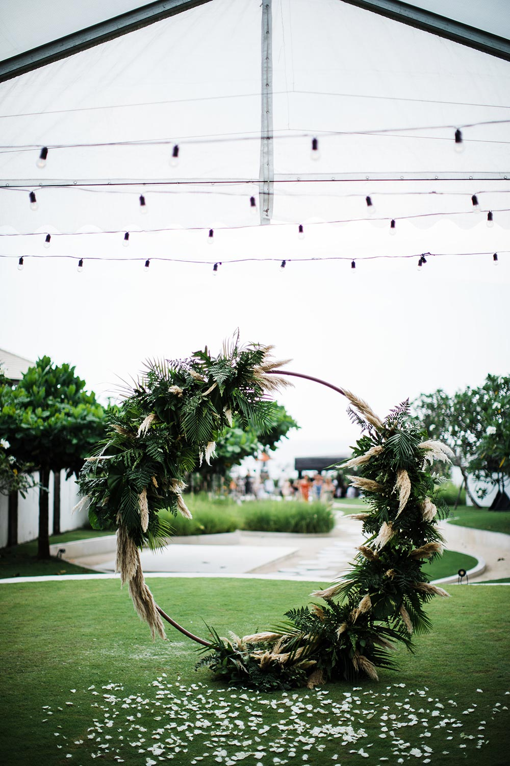 pampas grass and palm frond round wedding ceremony arbor