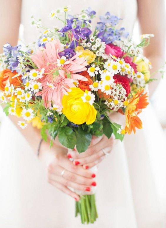 a very colorful wedding bouquet in pink, fuchsia, yellow and purple with a messy wildflower-inspired look